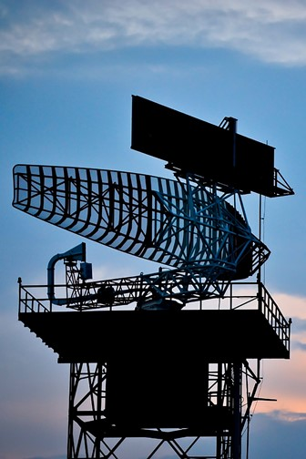 silhouetted radar tower and airplane