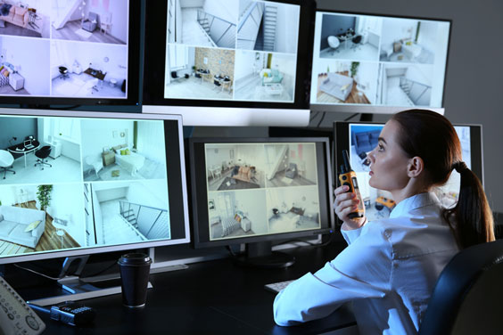 female security guard monitoring multiple CCTV cameras on computer screens